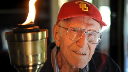 Louis Zamperini, 94, at his Hollywood home. The flame still burns in him as he holds the olympic torch he carried at the 1984 Olympic Games. Photo by Brad Graverson 11-7-10