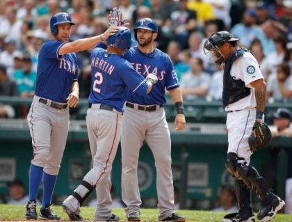 Leonys Martin #2 of the Texas Rangers is congratulated by David Murphy #7 and Mitch Moreland #18 after hitting a three-run homer against the Seattle Mariners in the second inning at Safeco Field on August 28, 2013 in Seattle, Washington.  (Photo by Otto Greule Jr/Getty Images)