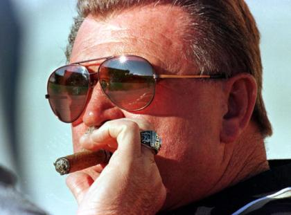 CHICAGO, UNITED STATES:  Soldier Field is reflected in the glasses of New Orleans Saints coach Mike Ditka as he smokes a cigar prior to the game against the Chicago Bears, 22 August, in Chicago, IL. This is Ditka's first appearance back at Soldier Field since he was coach of the Chicago Bears. AFP PHOTO VINCENT LAFORET (Photo credit should read VINCENT LAFORET/AFP/Getty Images)