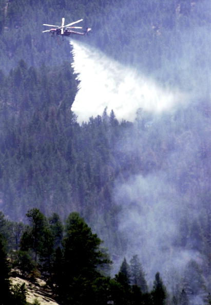 A helicopter dumps a load of water on a hot spot near the northern fire line of the Hayman fire, 16 June 2002 south of Buffalo Creek, Colorado.  The US Forest Service said Sunday it had arrested US Forest Service employee Terry Barton for setting one of several wildfires that have ravaged the western state of Colorado for the past several days, forcing thousands to flee their homes. The giant blaze near the state capital of Denver is the worst ever to hit Colorado, and has already consumed 43,700 hectares (108,000 acres), destroying homes, causing some 5,400 people to flee, and costing more than 20 million dollars.   AFP PHOTO/MARK LEFFINGWELL (Photo credit should read MARK LEFFINGWELL/AFP/Getty Images)