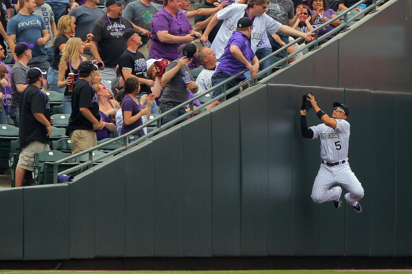 Leftfielder Carlos Gonzalez of the Colorado Rockies leaps against the wall to catch a foul ball at Coors Field on April 5, 2013.  (credit: Doug Pensinger/Getty Images)