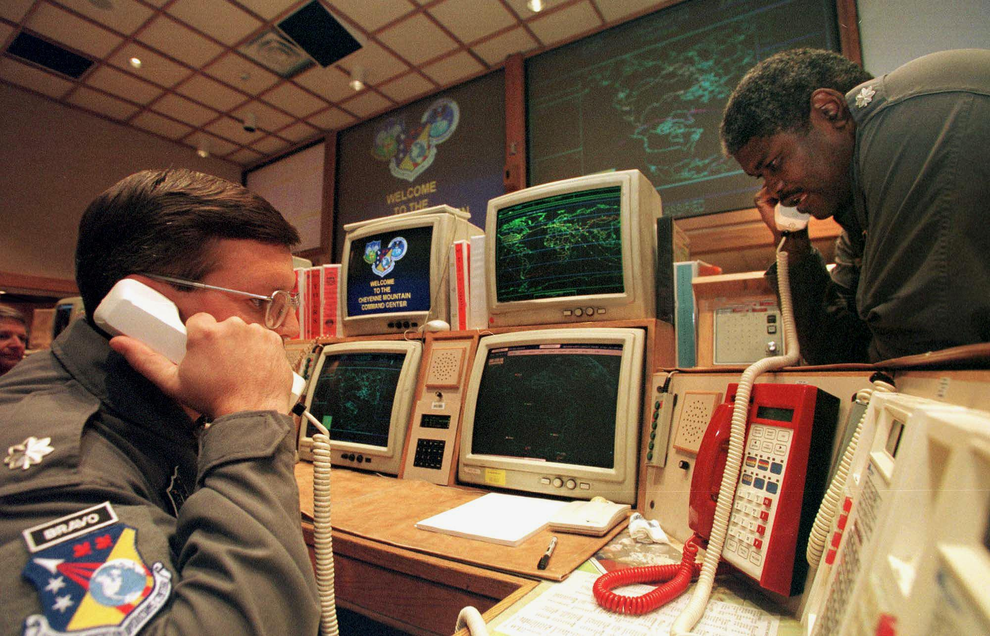 Missile Commanders Lt. (L) and Lt. Col. Ken Reed confirm a launch warning over the phone during a practice drill at the North America Aerospace Defense Command (NORAD) Cheyenne Mountain Complex in November 1999.  (credit: MARK LEFFINGWELL/AFP/Getty Images)