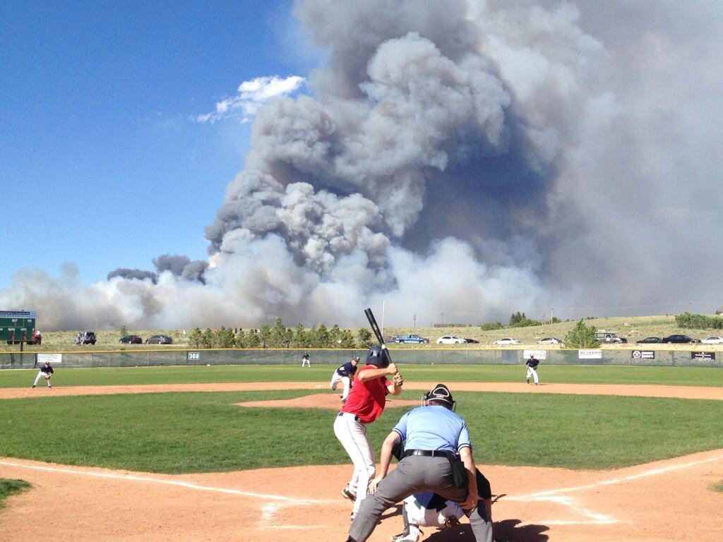 A baseball game going on with the Black Forest Fire in the background (credit: Peter McEvoy)
