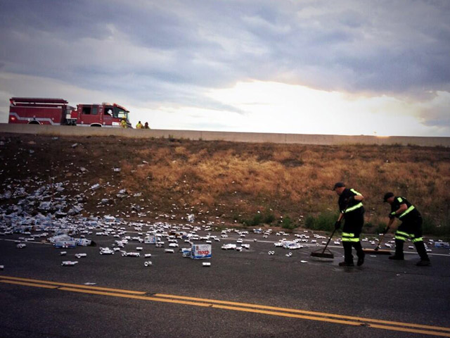 A semi truck rolled over on the Hwy 58 ramp to I-70 and spilled thousands of cans of beer onto the road. (credit: Wheat Ridge Police)