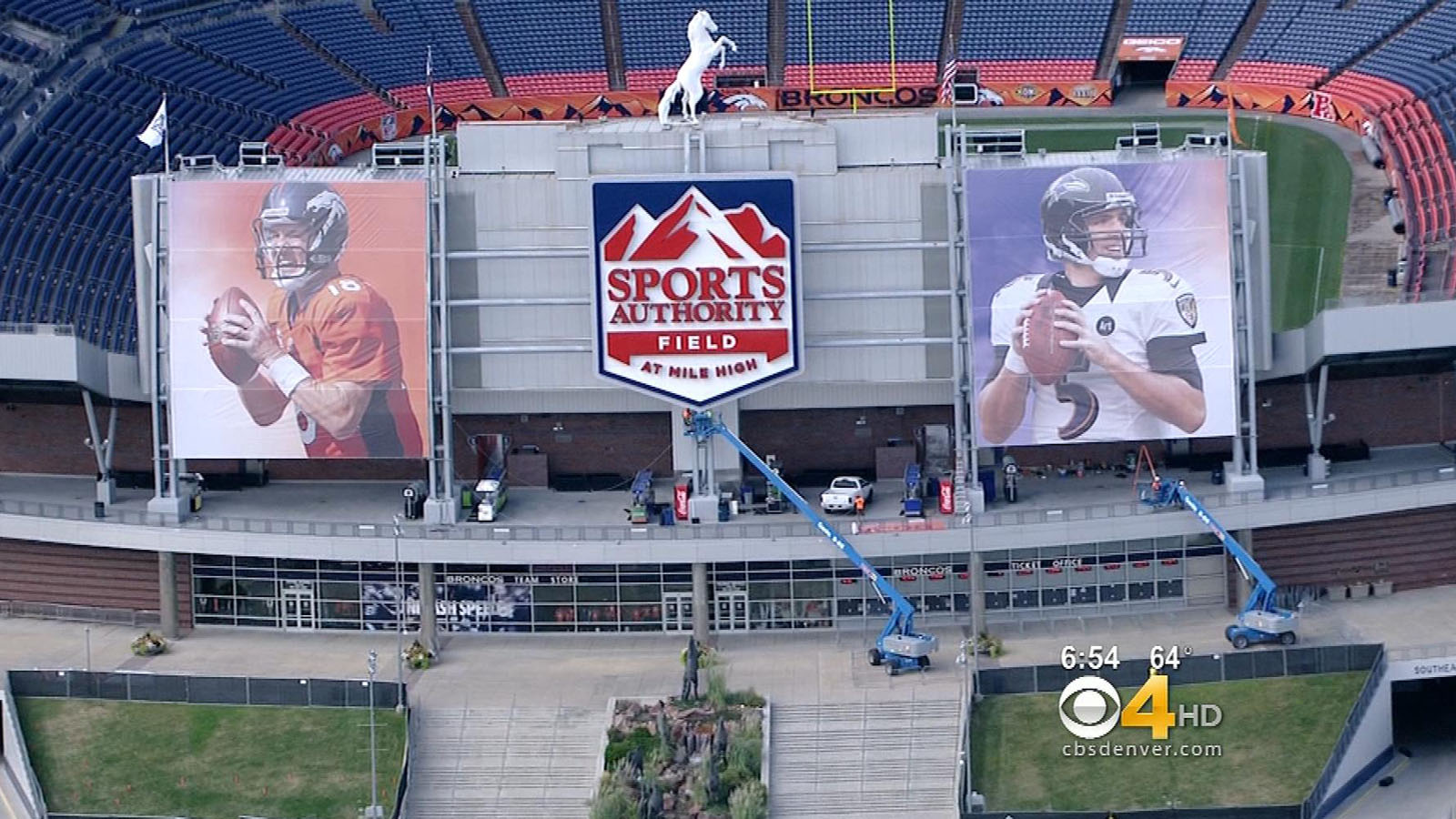Peyton Manning and Joe Flacco's images are shown on screens outside Sports Authority Field at Mile High on Aug. 27, 2013. (credit: CBS)