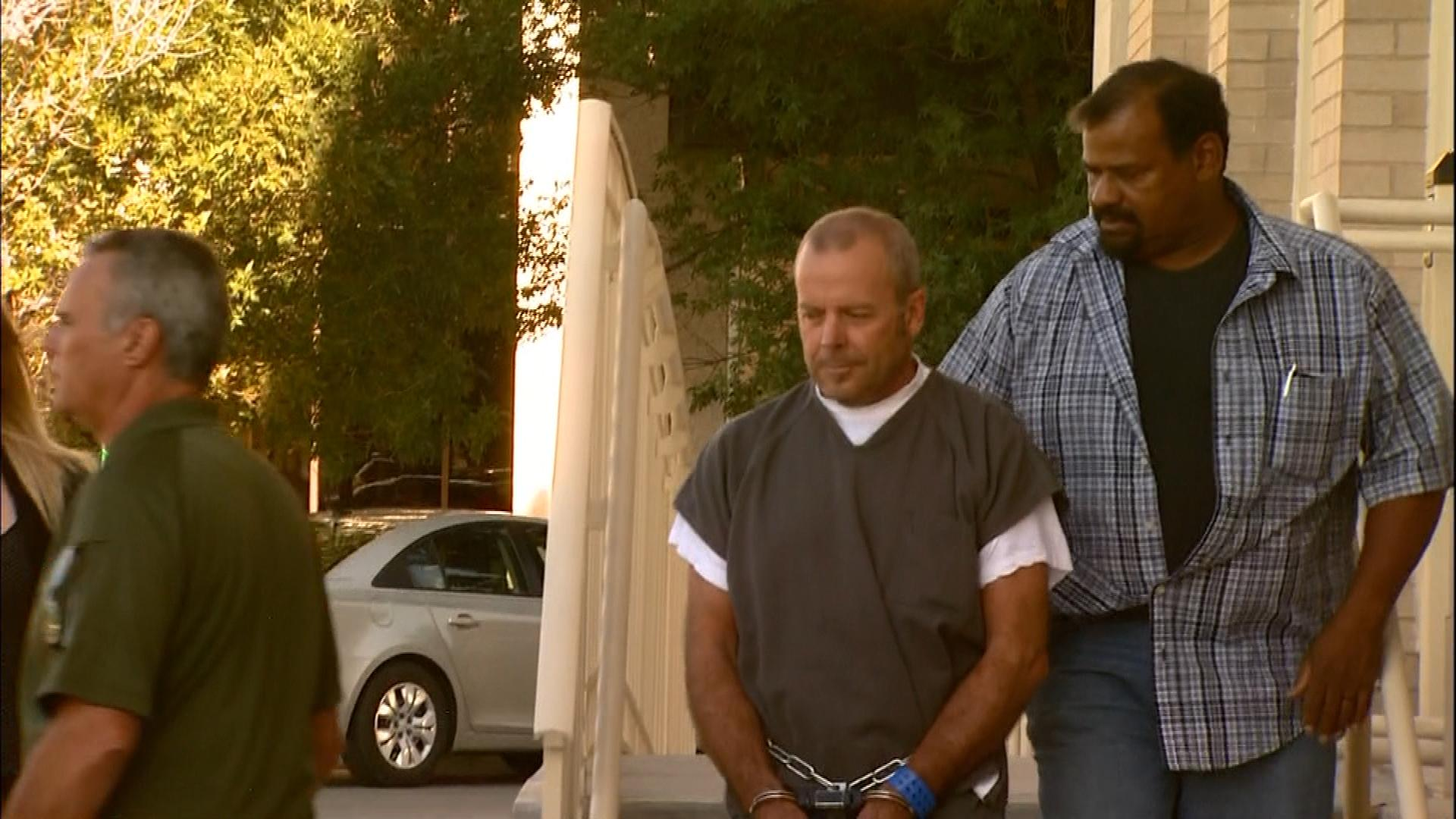 Dr. Joel Miller being escorted from court in August of 2013 (credit: CBS)