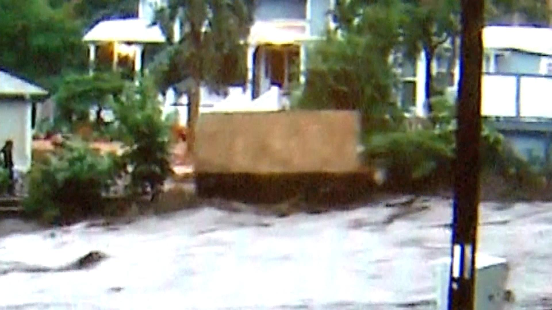 A still image from video taken by Jim Wilson's son of a piece of Laura Hunter's cottage being swept away with her inside (credit; CBS)