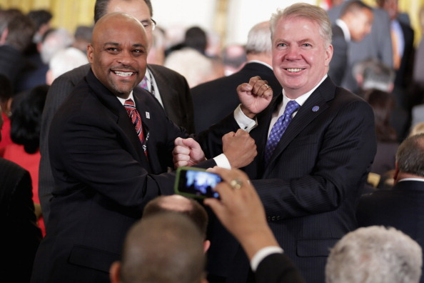 Denver Mayor Michael Hancock (L) and Seattle Mayor Ed Murray pretend to fight while posing for photographs during a reception with about 250 mayors from across the country in the East Room of the White House January 23, 2014 in Washington, DC. The NFL teams from Seattle and Denver are facing each other in the Super Bowl.  (Photo by Chip Somodevilla/Getty Images)