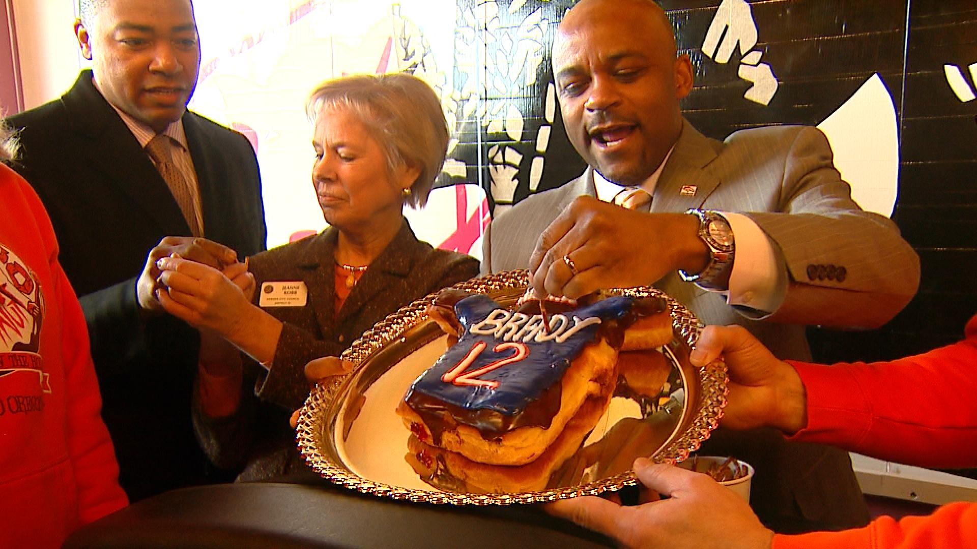 Denver Mayor Michael Hancock stabs the Tom Brady Voodoo Doughnut with a pretzel on Wednesday. (credit: CBS)