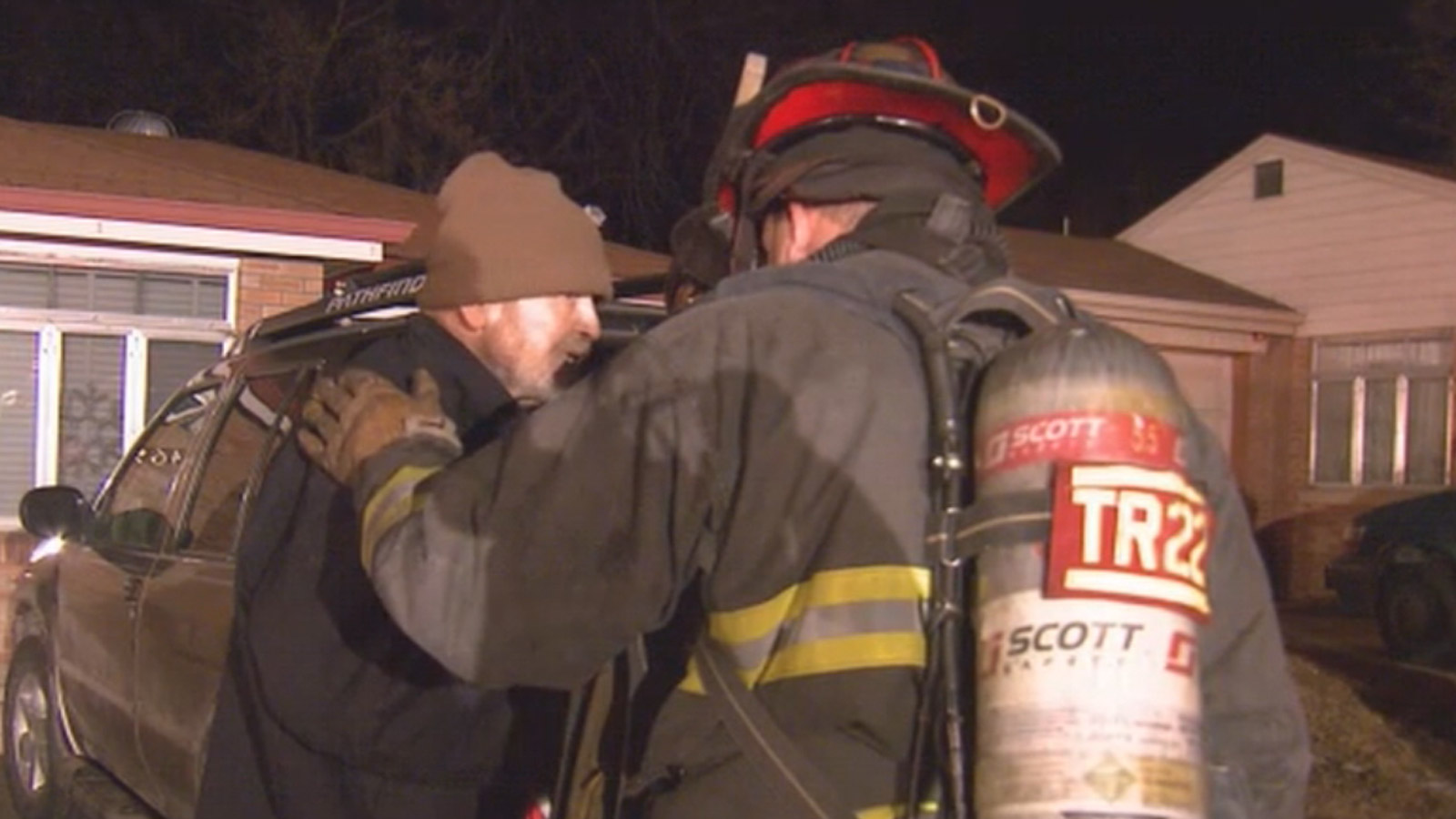 A firefighter comforts the homeowner's son after an early morning fire destroyed the home in the 1400 block of Bellaire Street. (credit: CBS)