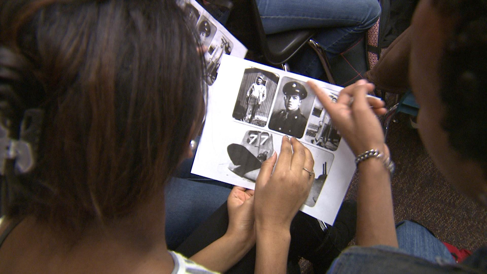 South High School students look at their guests' photos from World War II. (credit: CBS)