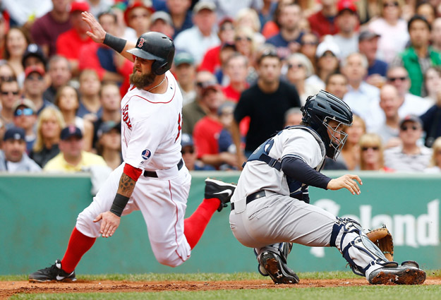 BOSTON, MA - SEPTEMBER 14: Mike Napoli #12 of the Boston Red Sox slides safely into home plate past J.R. Murphy #66 of the New York Yankees in the 5th inning to score during the game on September 14, 2013 at Fenway Park in Boston, Massachusetts.