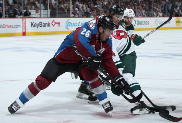 Paul Stastny #26 of the Colorado Avalanche and Mikael Granlund #64 of the Minnesota Wild battle for control of the puck in Game Five of the First Round of the 2014 NHL Stanley Cup Playoffs at Pepsi Center on April 26, 2014 in Denver, Colorado. (Photo by Doug Pensinger/Getty Images)