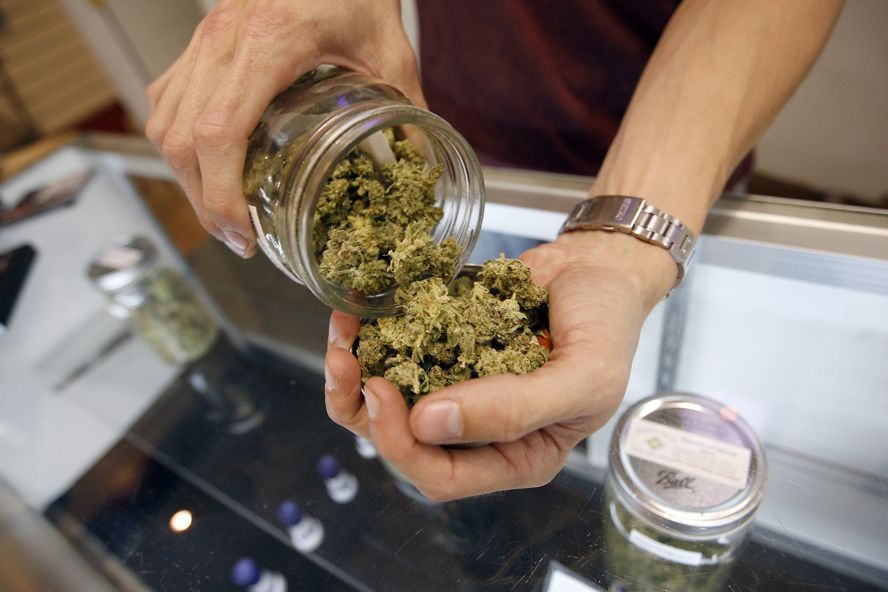 A budtender pours marijuana from a jar at a medical marijuana dispensary. (credit: David McNew/Getty Images)