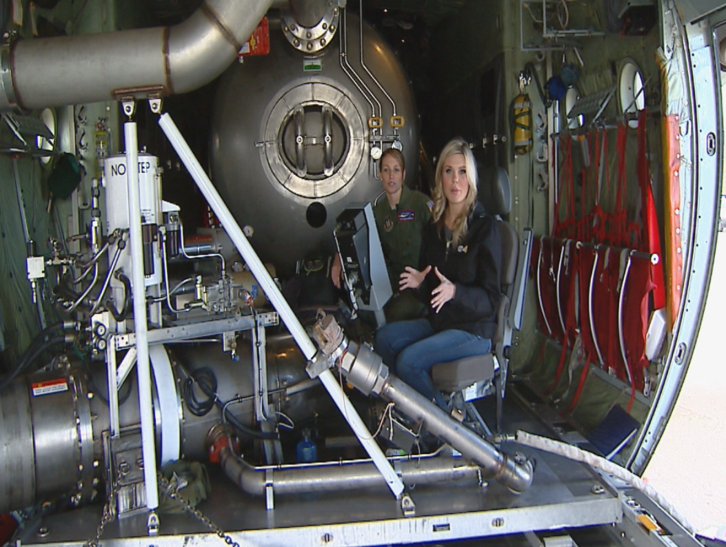 Lauren Whitney sits at the control panel in the back of a C-130 where crew members coordinate the water and slurry drops while fighting a wildfire from the air. (credit: CBS)
