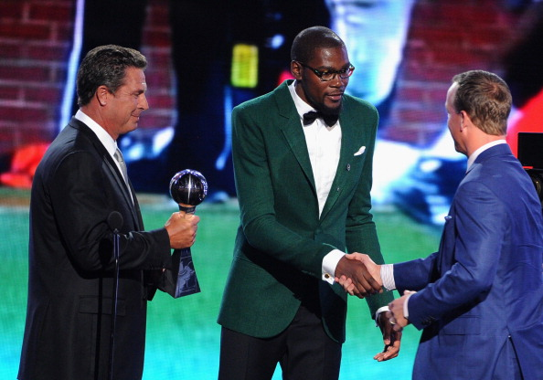 NFL player Peyton Manning of the Denver Broncos (R) accepts the Best Record-Breaking Performance award from former NFL player Dan Marino (L) and NBA player Kevin Durant (C) onstage during the 2014 ESPYS at Nokia Theatre L.A. Live on July 16, 2014 in Los Angeles, California.  (Photo by Kevin Winter/Getty Images)