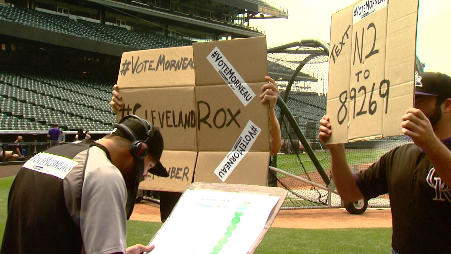 Rockies players holding up signs asking fans to vote for Justin Morneau while he was doing TV interviews on Tuesday (credit: CBS)