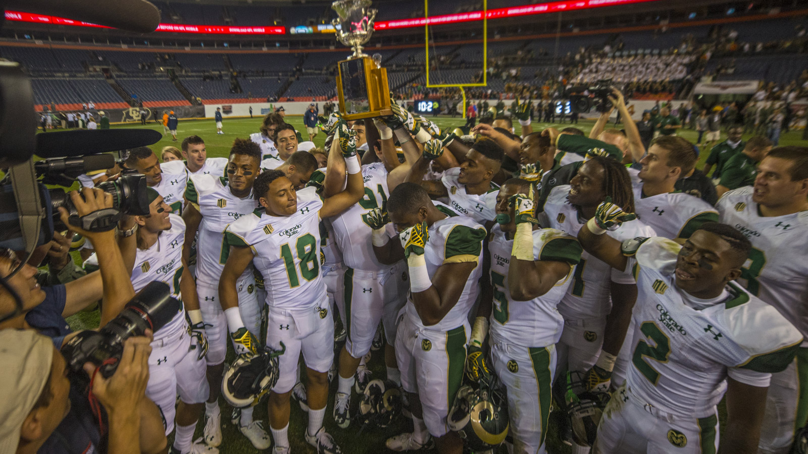 CSU Rams players celebrate with the Centennial Cup after defeating the the CU Buffaloes 31-17 in the Rocky Mountain Showdown at Sports Authority Field at Mile High on Aug. 29, 2014. (credit: Evan Semón/CBS4)