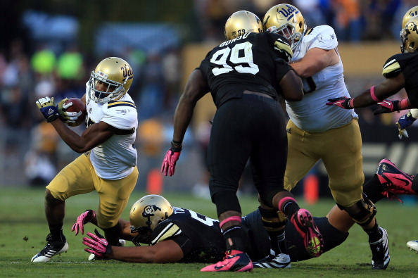 CU defensive lineman Josh Tupou tackles UCLA wide receiver Damien Thigpen in a game in 2012 in Boulder. (Photo by Doug Pensinger/Getty Images)