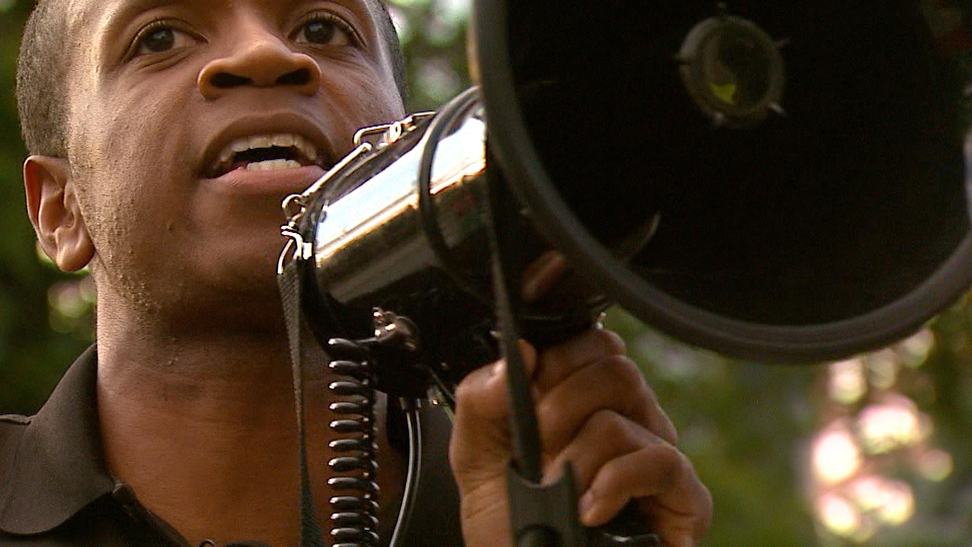 Kenny Wiley speaks through a megaphone at the rally. (credit: CBS)