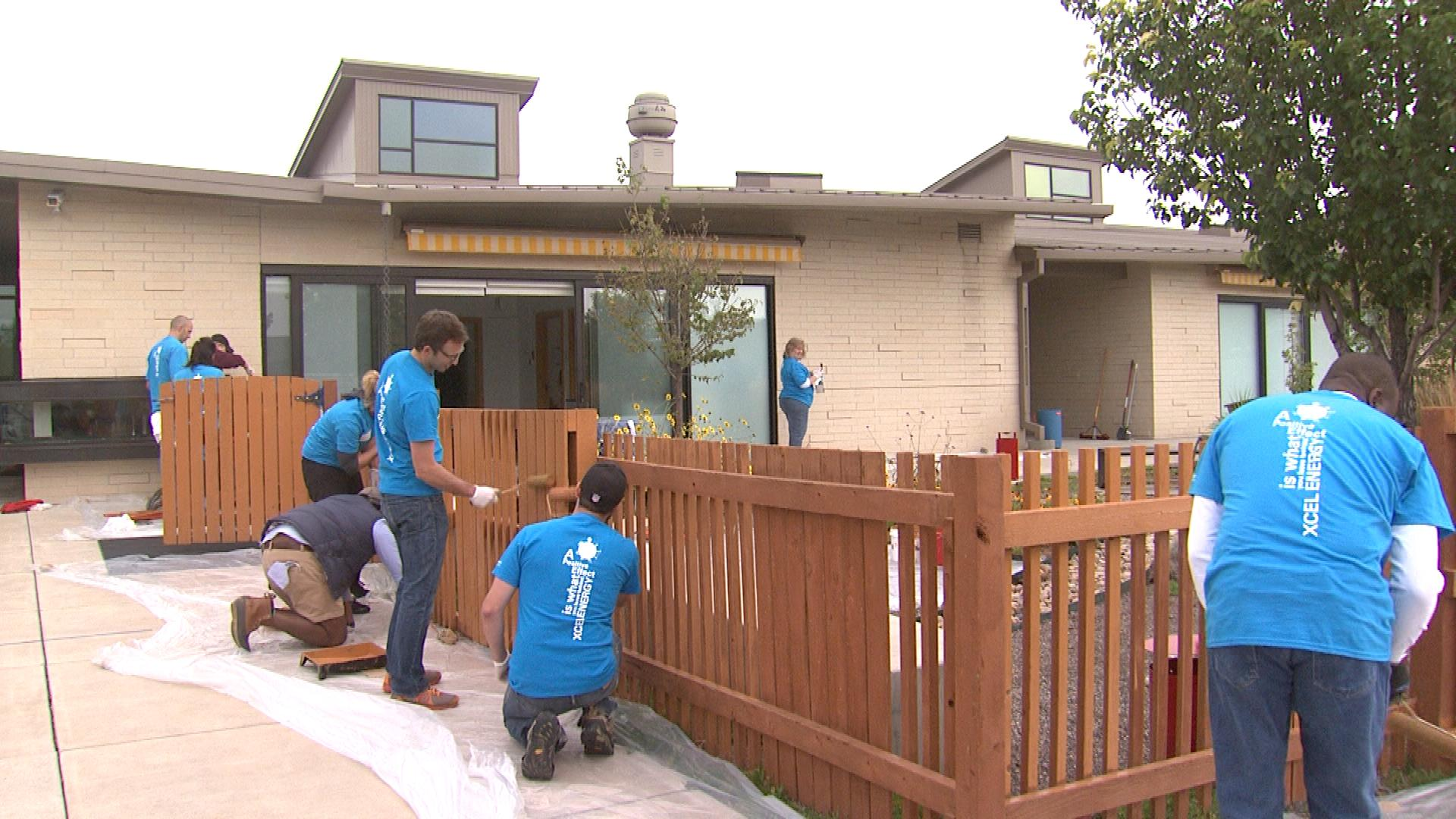 Volunteers paint a fence at the Anchor School for Blind Children (credit: CBS)
