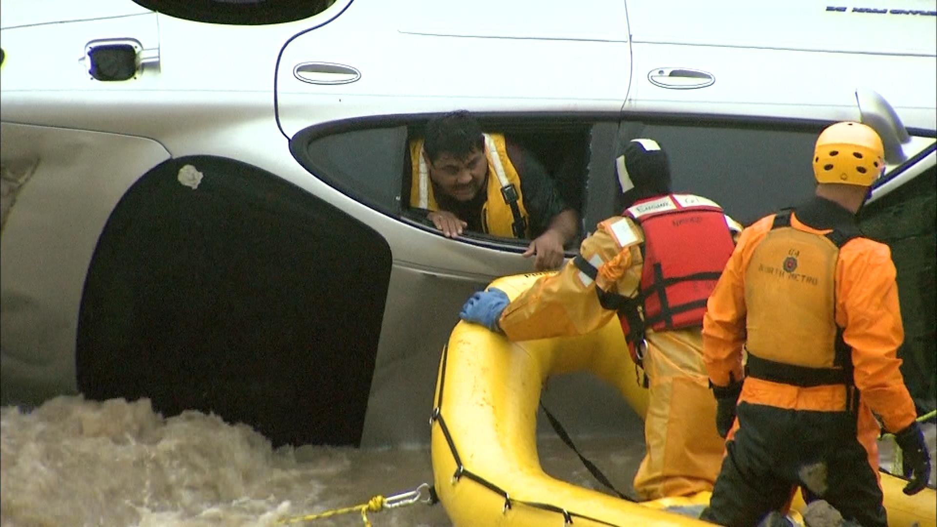 Rescuers start extracting the man from his overturned car. (credit: CBS)