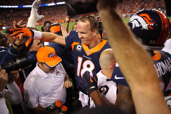 Quarterback Peyton Manning #18 of the Denver Broncos celebrates with teammates and the coaching staff on the sideline after throwing his NFL record 509th career touchdown pass in the second quarter of a game against the San Francisco 49ers at Sports Authority Field at Mile High on October 19, 2014 in Denver, Colorado.  (Photo by Justin Edmonds/Getty Images)