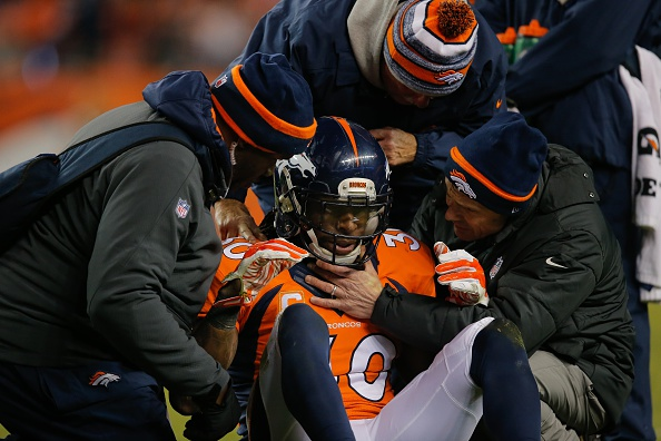 Strong safety David Bruton #30 of the Denver Broncos is attended to by trainers after a play that would force him out of the game with a reported concussion during a game against the Oakland Raiders at Sports Authority Field at Mile High on December 28, 2014 in Denver, Colorado.  (Photo by Doug Pensinger/Getty Images)