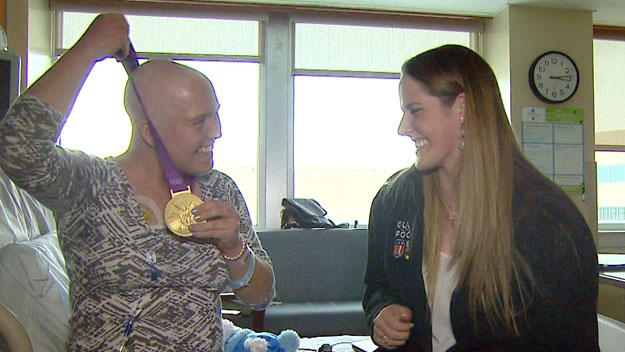 Rebecca Carcaterra tries on Missy Frankin's gold medal (credit: CBS)