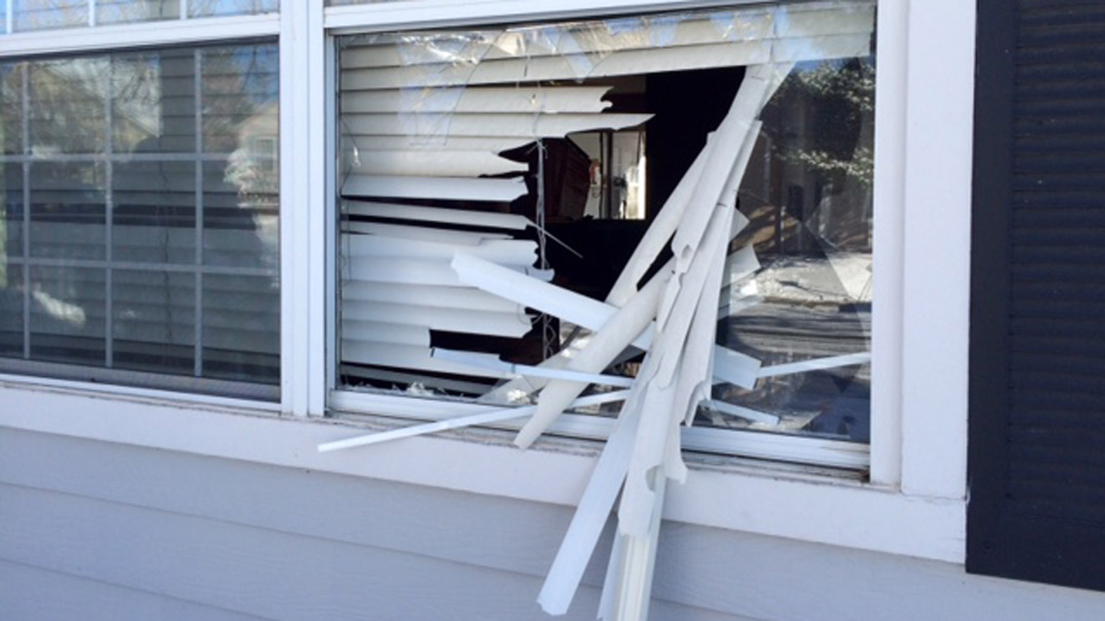A broken window at an Arvada home where one or more of the arrests happened. (credit: CBS)