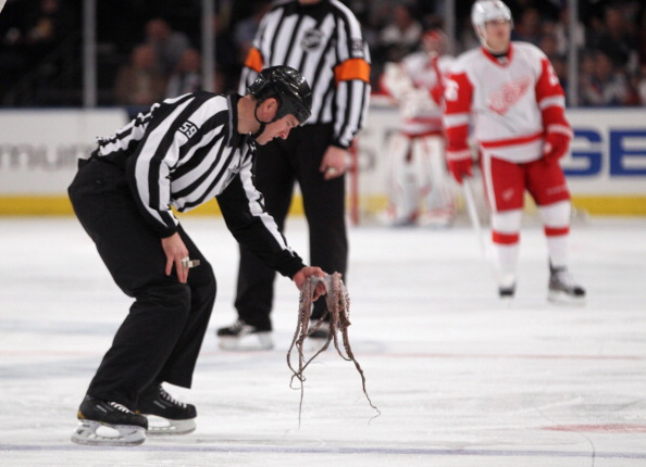 Linesman Steve Barton #59 removes an octopus from the ice following a first period goal by Henrik Zetterberg #40 of the Detroit Red Wings against the New York Rangers at Madison Square Garden on March 21, 2012 in New York City.  (Photo by Bruce Bennett/Getty Images)