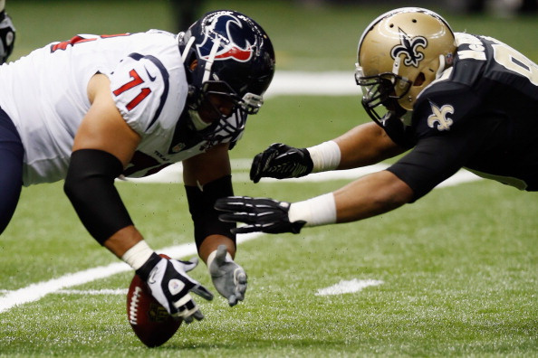 Shelley Smith #71 of the Houston Texans and  Turk McBride #90 of the New Orleans Saints fight for a fumble at the Mercedes-Benz Superdome on August 25, 2012 in New Orleans, Louisiana.  (Photo by Chris Graythen/Getty Images)