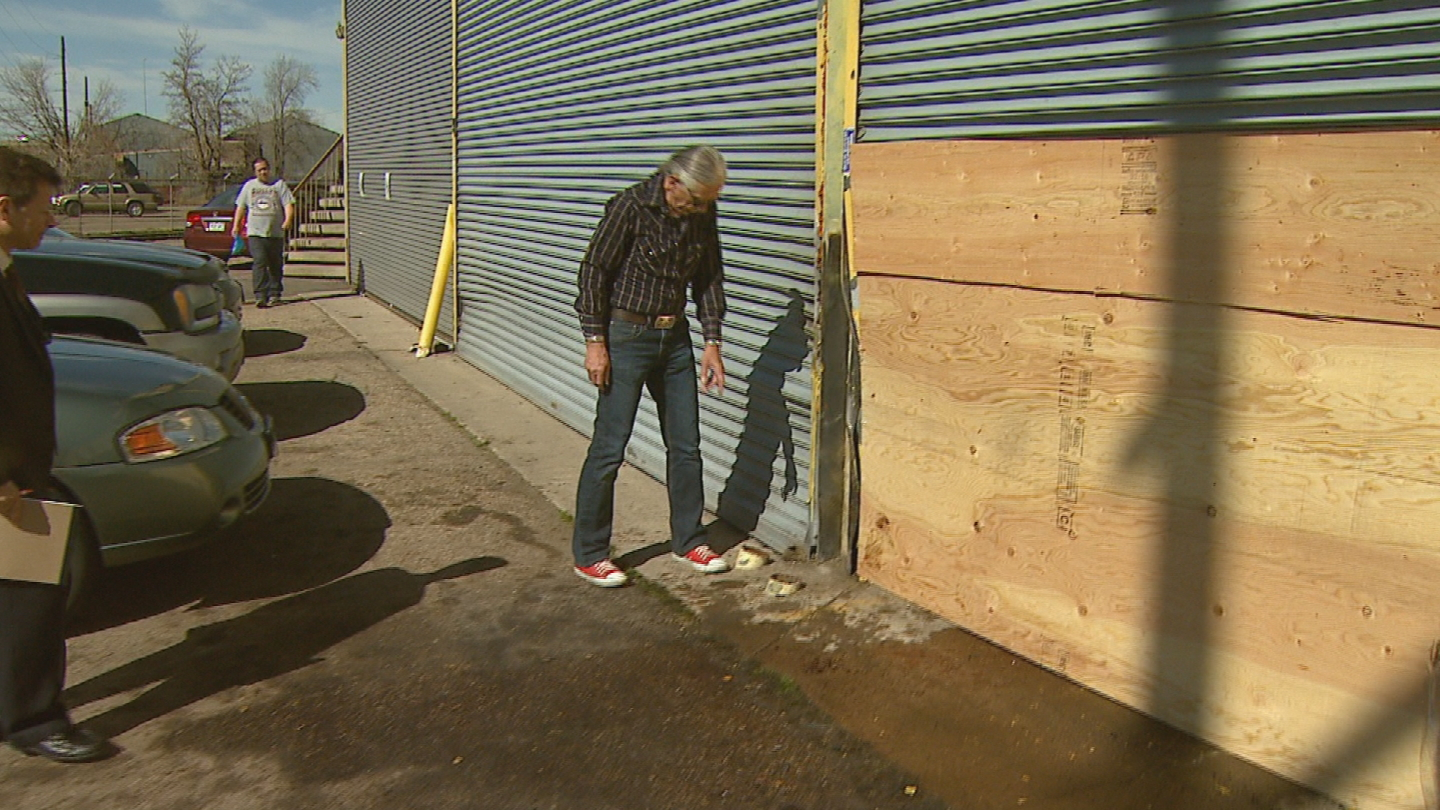 Chuck Rozanski shows where steel poles should be outside his store (credit: CBS)