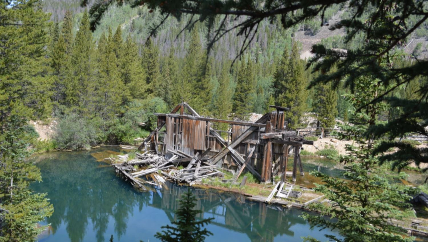 Today, the Reiling Dredge still sits in a small pond of its own creation, showing the effects of time and nature. (credit: Breckenridge Heritage Alliance)