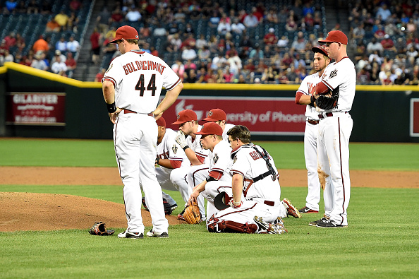 Paul Goldschmidt #44 of the Arizona Diamondbacks and the rest of the starting lineup look on as teammate Archie Bradley #25 is tended to on the pitchers mound after getting hit in the face with a line drive against the Colorado Rockies at Chase Field on April 28, 2015 in Phoenix, Arizona.  (Photo by Norm Hall/Getty Images)