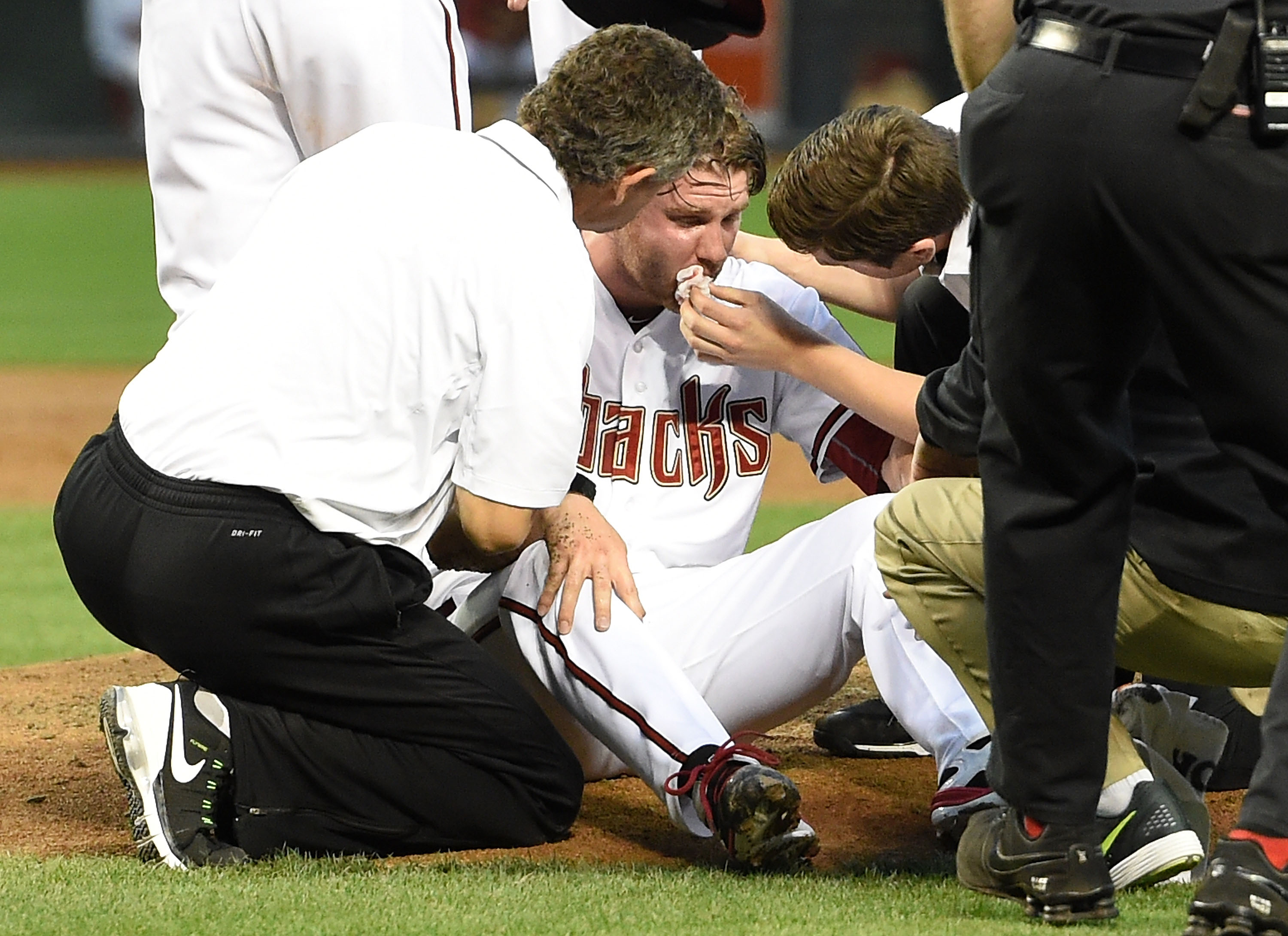 Archie Bradley #25 of the Arizona Diamondbacks is tended to on the pitcher's mound after getting hit in the face with a line drive against the Colorado Rockies at Chase Field on April 28, 2015 in Phoenix, Arizona.  (Photo by Norm Hall/Getty Images)