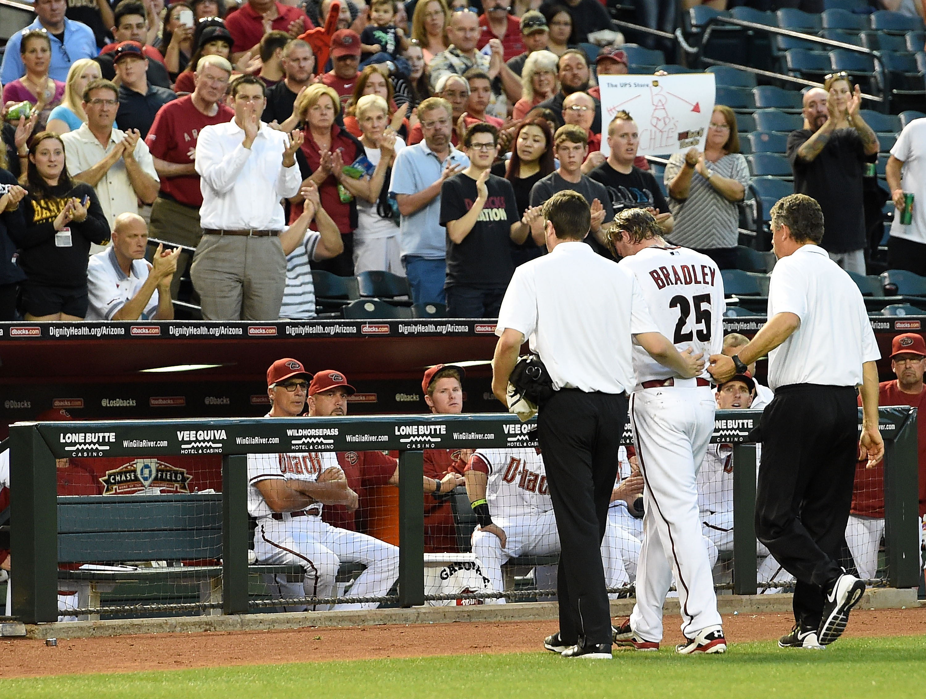 Fans cheer on pitcher Archie Bradley #25 of the Arizona Diamondbacks as he is helped off the field after getting hit in the face with a line drive against the Colorado Rockies at Chase Field on April 28, 2015 in Phoenix, Arizona.  (Photo by Norm Hall/Getty Images)