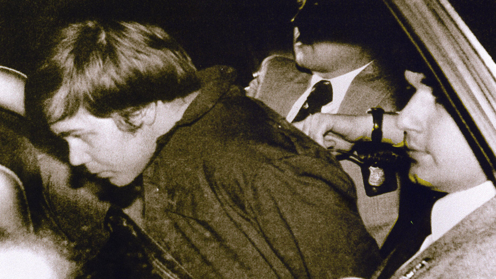 This 30 March 1981 file photo shows John Hinckley Jr. (L) escorted by police in Washington, DC, following his arrest after shooting and seriously wounding then US president Ronald Reagan. A federal judge ruled 17 December 2003 Hinckley can make local visits with his family from St. Elizabeth's Hospital in Washington, DC, where he has been held. AFP PHOTO/FILES (credit: AFP/Getty Images)