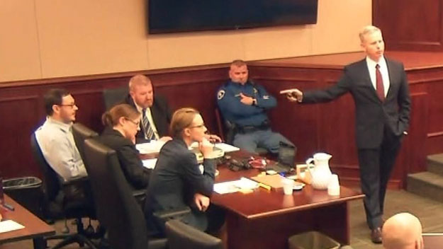 District Attorney George Brauchler points at James Holmes, who sits with his defense team in court on April 27, 2015. (credit: CBS)