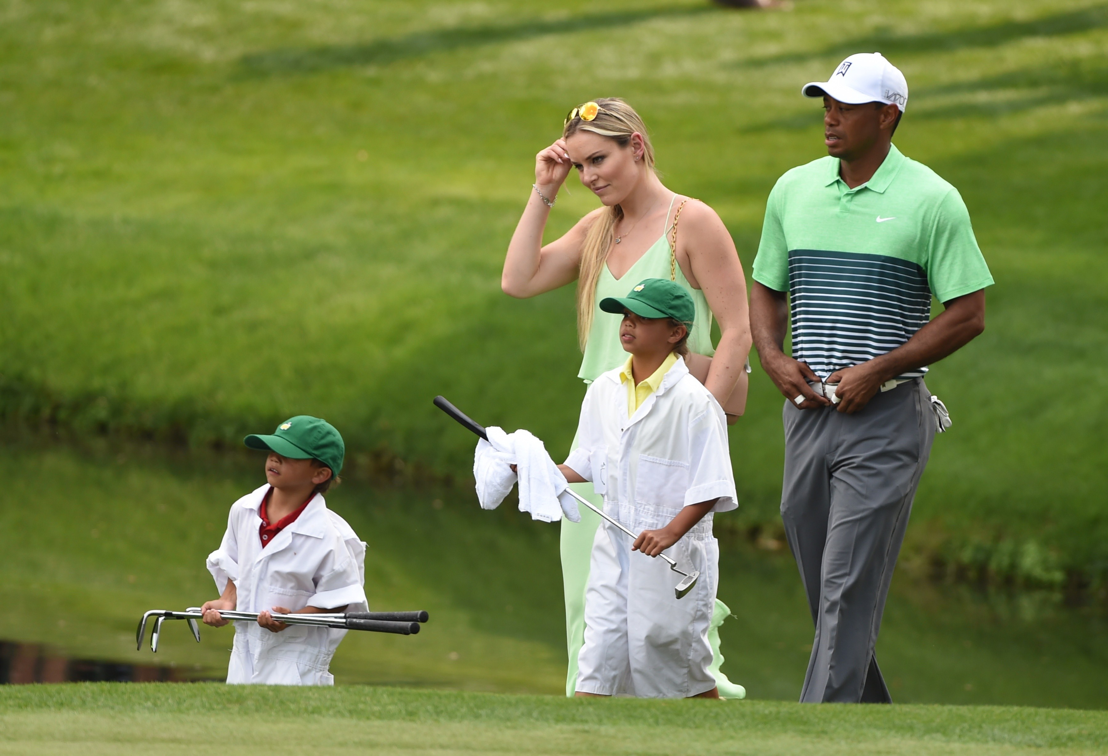 Tiger Woods of the US (R) walks with US Skier Lindsey Vonn, daughter Sam Alexis and son Charlie Axel during the Par 3 competition on April 8, 2015, at Augusta National Golf Club in Augusta, Georgia. The competition is part of the Masters Golf Championship which starts April 9. AFP PHOTO/TIMOTHY A. CLARY        (Photo credit should read TIMOTHY A. CLARY/AFP/Getty Images)