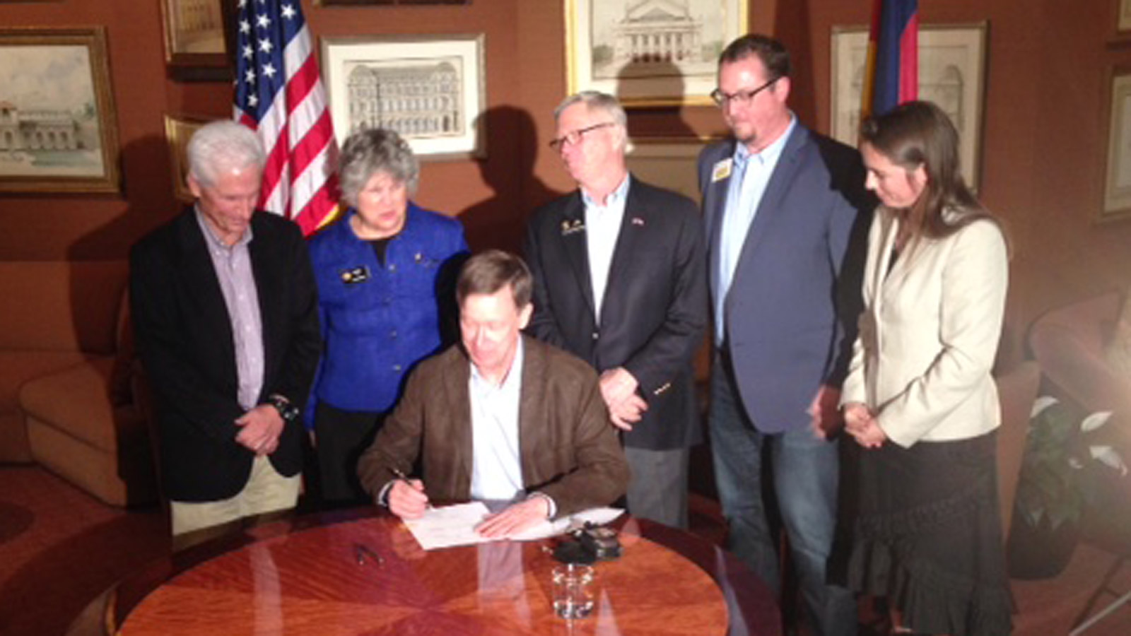 Gov. John Hickenlooper signs a bill into law that will study chains and snow tires for all vehicles on I-70 (credit: CBS)