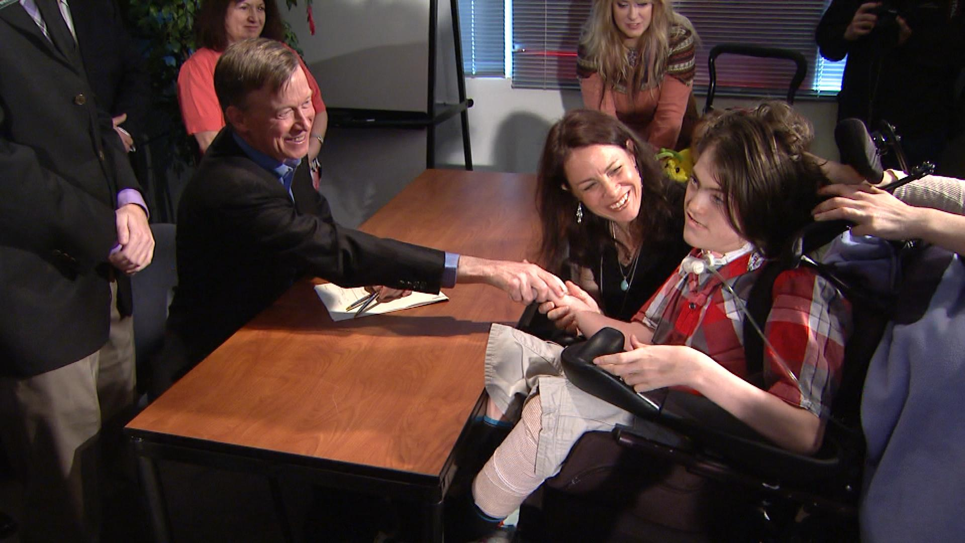 Gov. John Hickenlooper shakes Jack Splitt's hand after signing the bill into law (credit: CBS)