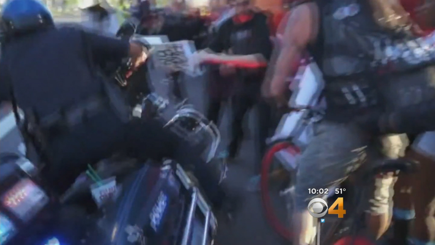 Denver police officer's motorcycle falls over beside protesters (credit: Jesse Benn)