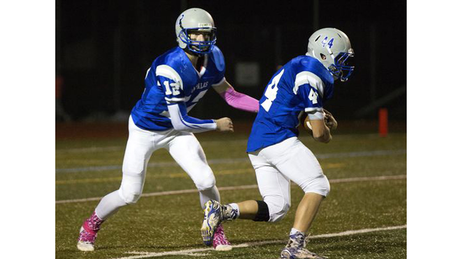 Poudre High School quarterback Taylor Gaes is on the left, player #12, handing off ball during a 2014 football game (credit: Coloradoan Library)