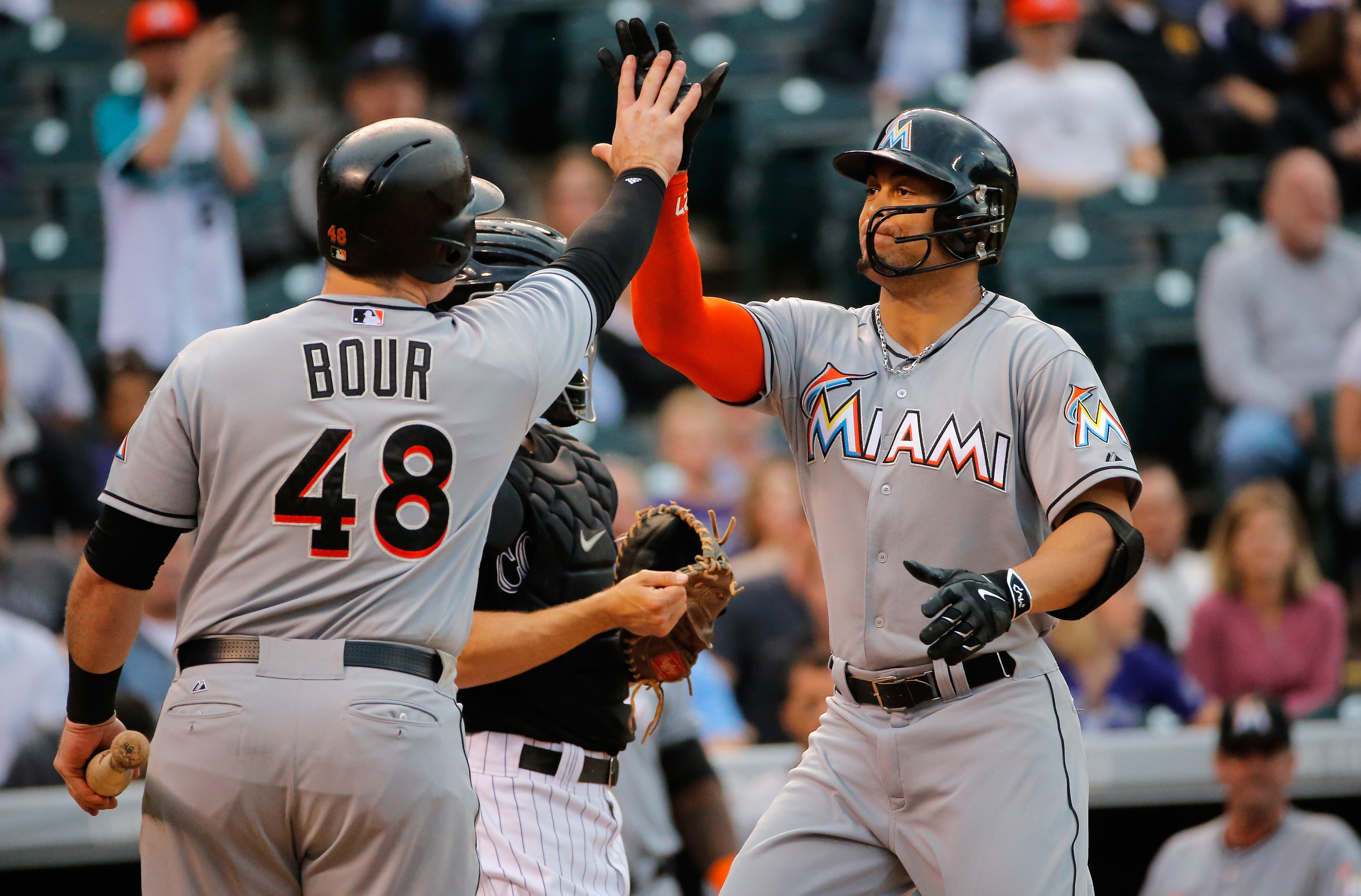 Giancarlo Stanton #27 of the Miami Marlins celebrates his solo home run off of Eddie Butler #31 of the Colorado Rockies with Justin Bour #48 of the Miami Marlins as the Marlins take a 3-0 lead in the third inning at Coors Field on June 5, 2015 in Denver, Colorado. (Photo by Doug Pensinger/Getty Images)