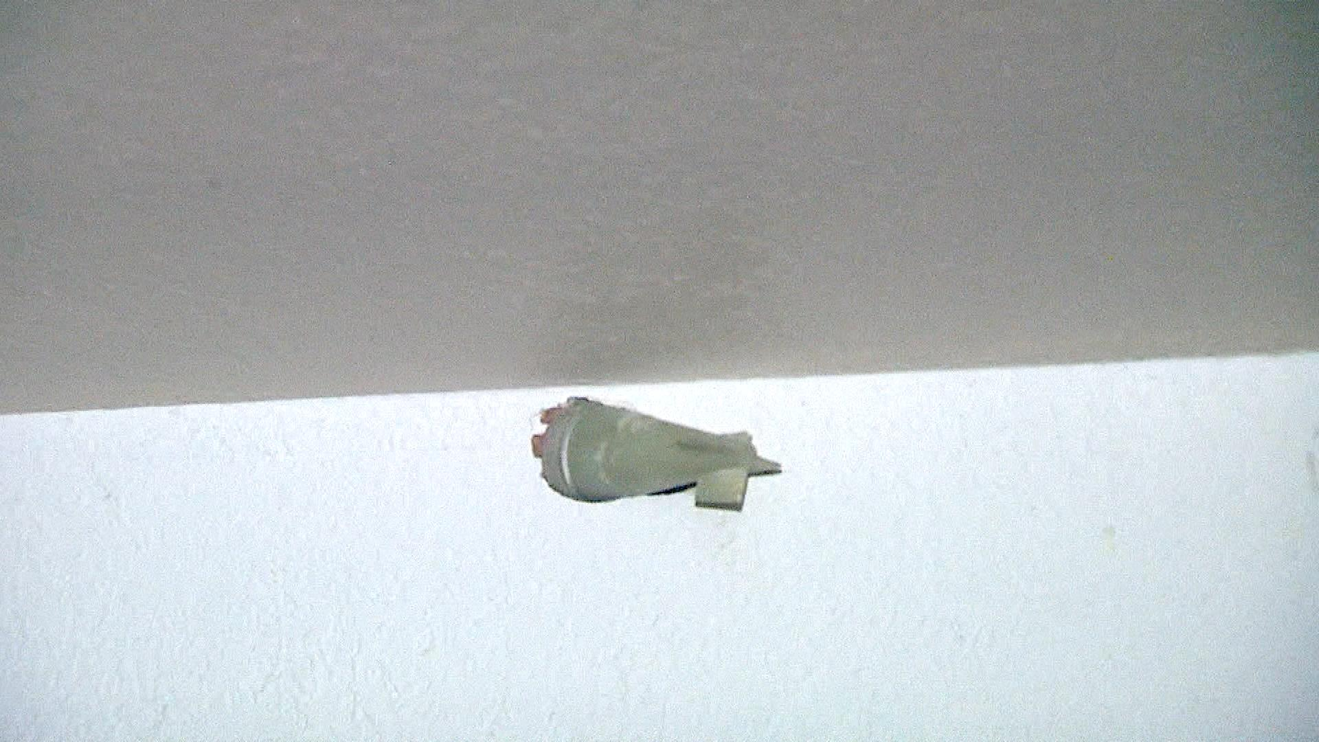 An explosive stuck in the wall (credit: CBS)