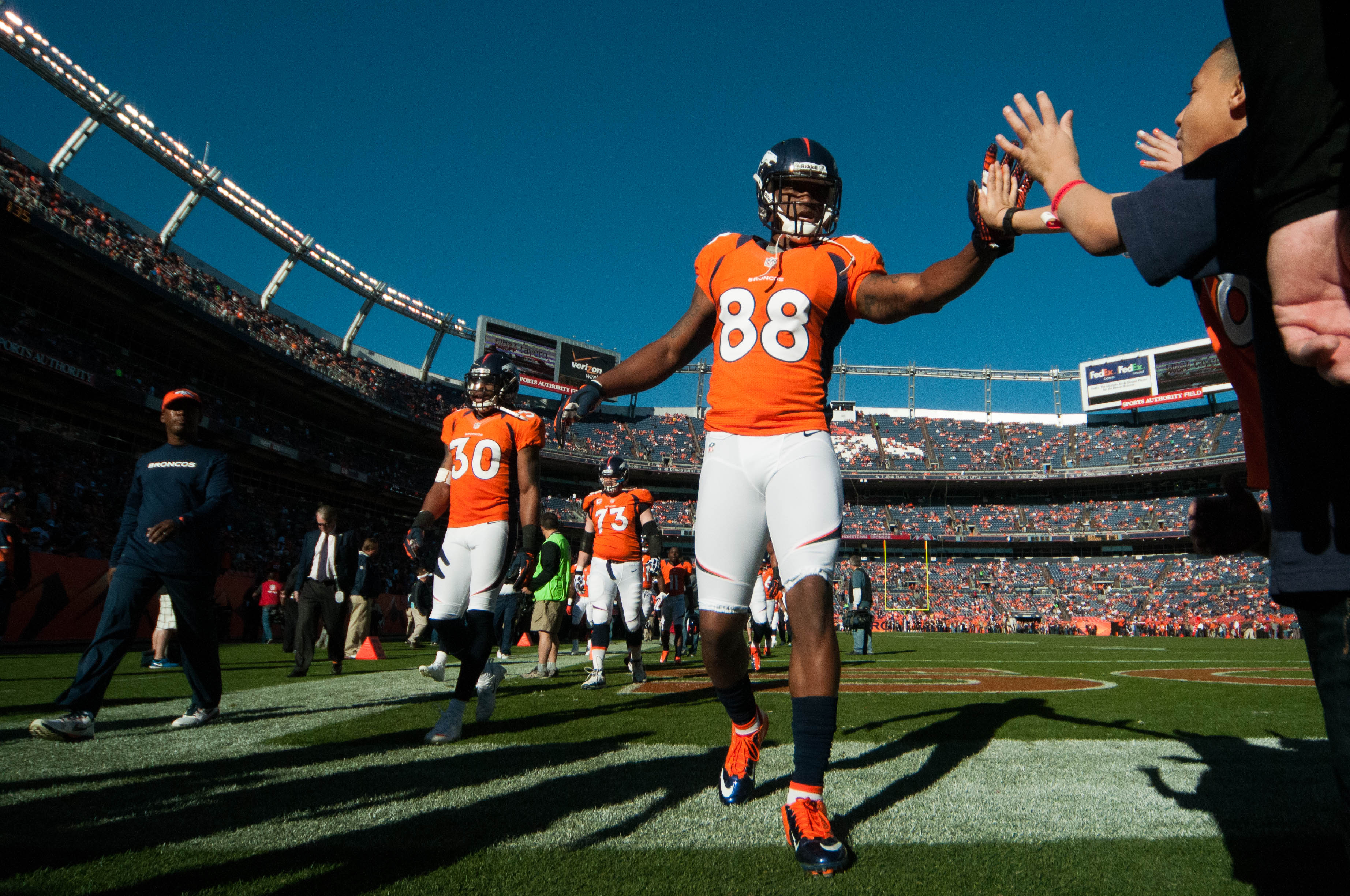 DENVER, CO - DECEMBER 2: Wide receiver Demaryius Thomas #88 of the Denver Broncos gives supporters high fives as he goes into the locker room after warming up before the game against the Tampa Bay Buccaneers at Sports Authority Field at Mile High on December 2, 2012 in Denver, Colorado. (Photo by Dustin Bradford/Getty Images)
