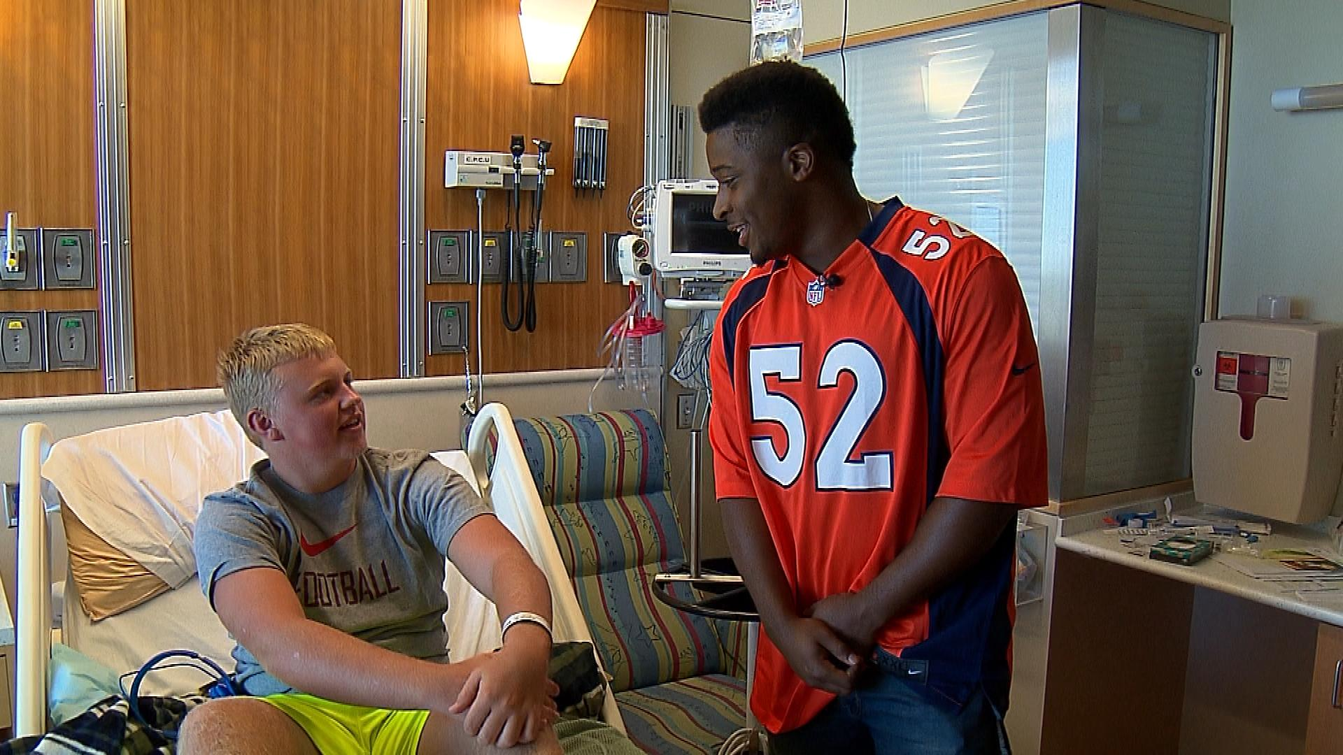 Corey Nelson visits with a patient at Children's Hospital (credit: CBS)