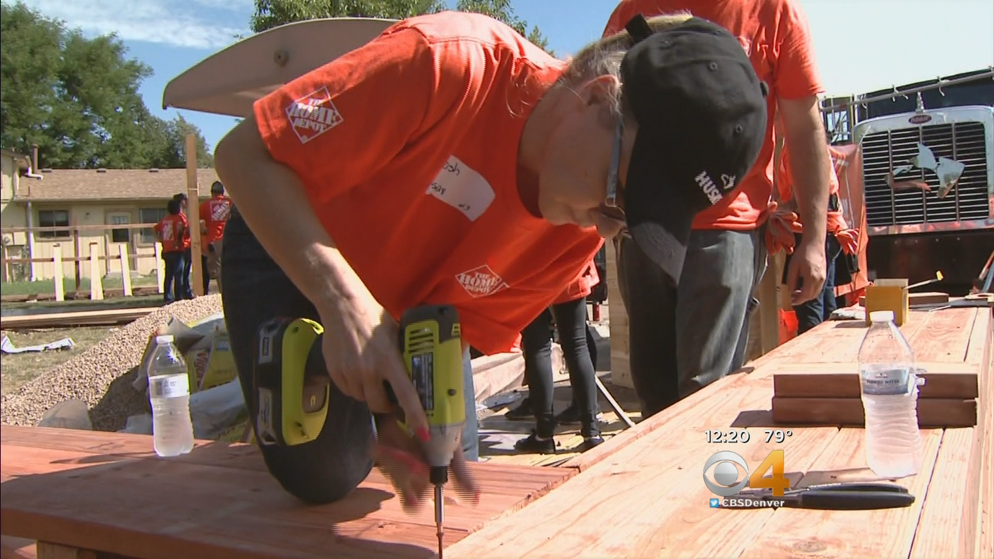 Home Depot volunteers helped a veteran's widow reclaim her yard (credit: CBS)