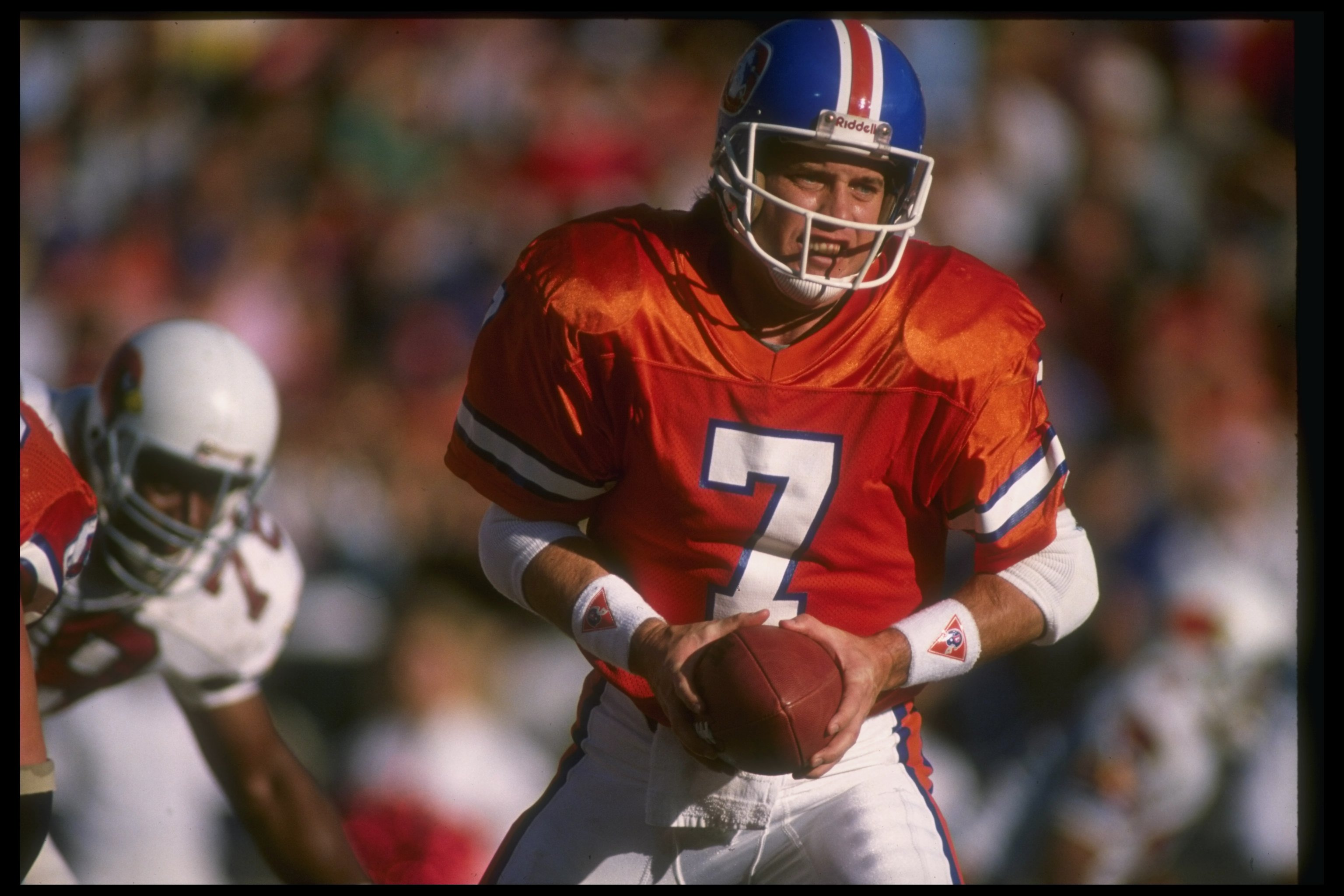 Quarterback John Elway of the Denver Broncos prepares to hand off the ball during a game against the Arizona Cardinals at Mile High Stadium in Denver on Dec. 16, 1989. The Broncos won the game, 37-0. (credit: Stephen Dunn  /Allsport/Getty Images)